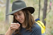 Mercedes Pisano admiring one of the very handsome skinks recorded during the survey. Photo by Leah Carr.<br/>