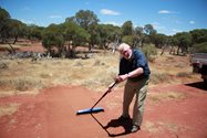 Brian Martin prepares the sandpad, sweeping it to create a smooth surface in which animal tracks can be identified.<br/>