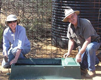 Volunteers put a temporary water trough in a goat trap. Photo Kurt and Andrea Tschirner.