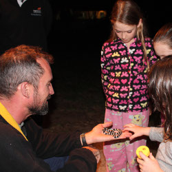 Andrew Amey shows the Wilson girls a Bandy Bandy snake found near Elbow dam