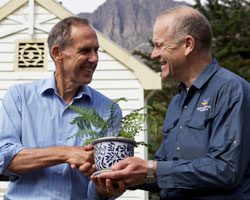 Photo of Doug Humann presenting Bob Brown with a fern grown from Liffey Valley stock